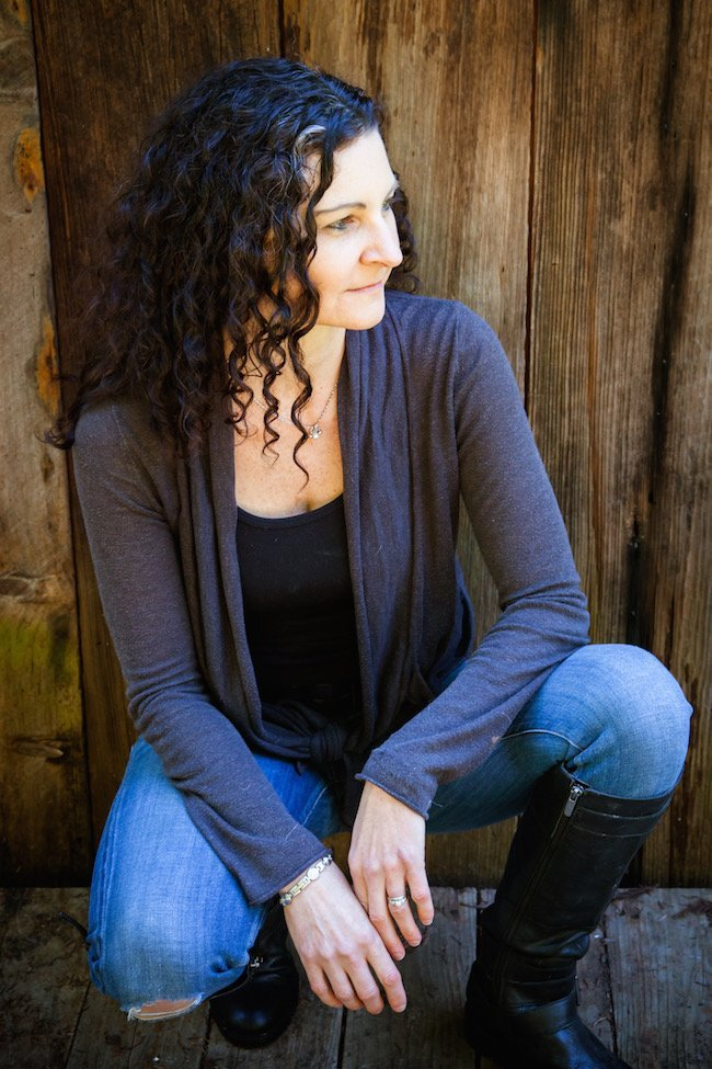 Woman in jeans in front of wooden fence